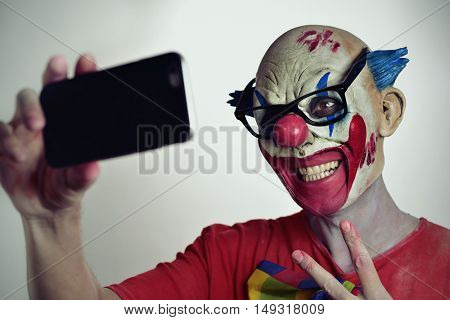 portrait of a scary evil clown taking a selfie with his smartphone, while giving a V sign