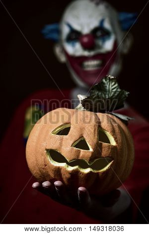 a scary evil clown holding a carved pumpkin in his hand