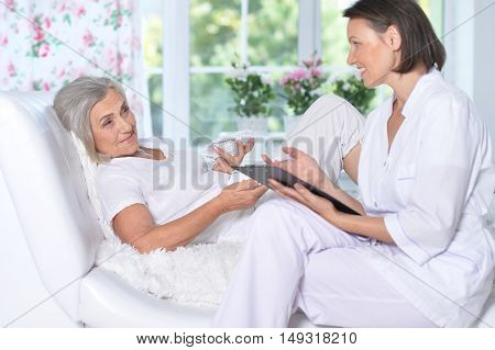 Senior woman portrait in hospital with caring doctor