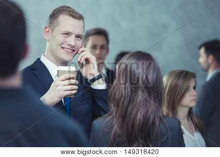 Young and happy boy talking on the phone among crowd of people