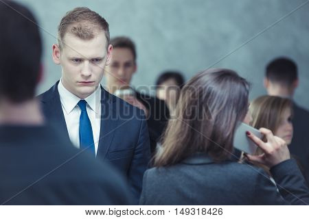 Businessman surrounded by the crowd of people