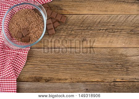 Grated chocolate in a glass bowl on the old wooden table. Top view.