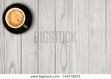 Coffee cup on white wooden table background. Top view with copy space