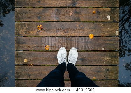 Top view male legs in sneakers on wooden bridge by fall time tree reflection on water. Autumn concept