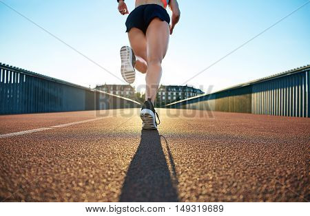Low angle view of female jogger bounding forward on a bright day towards apartment buildings