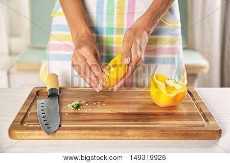 Woman slicing pepper on cutting board