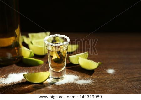 Gold tequila shot with lime and salt on wooden table