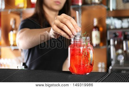 Woman hands putting straws into cocktail on bar counter