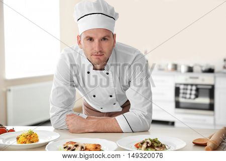 Young chef cook with different dishes in kitchen