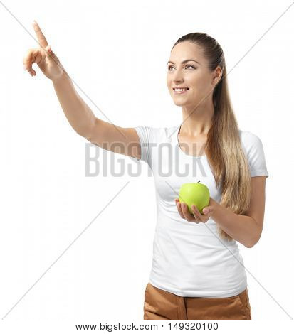 Beautiful girl with apple pointing finger, isolated on white