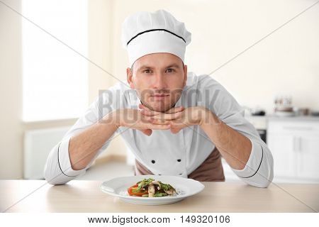 Young chef cook and tasty dish in kitchen