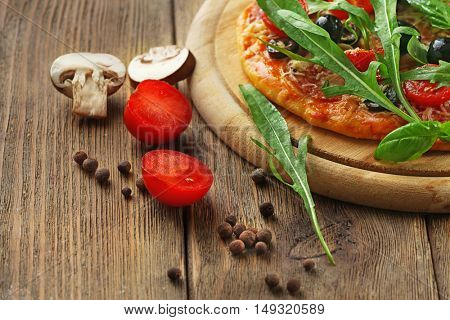 Tasty pizza with vegetables, herbs on wooden background