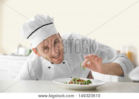 Young chef cook decorating dish in kitchen