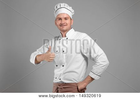 Young chef cook on grey background