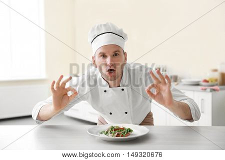 Young chef cook with dish on plate in kitchen