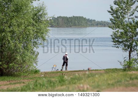 single fisherman catches a fish on the shore