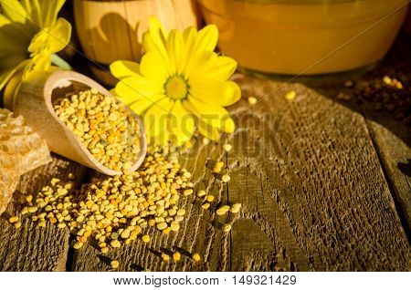Bee Pollen Granules  In Wooden Scoop And Flowers On Wooden Table