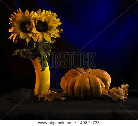 The pumpkins and sunflowers on a blue background
