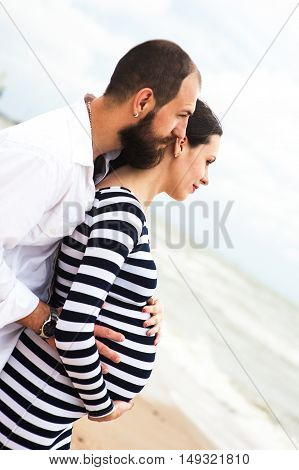 Beautiful young pregnant woman with man on the beach feel peace and tranquility