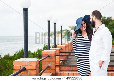 Beautiful young pregnant woman with man on the balcony feel peace and tranquility