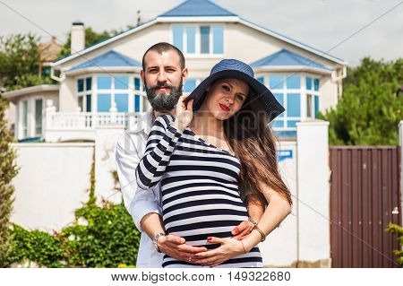 Beautiful young pregnant woman with man near the house feel peace and tranquility