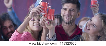 Group of smiled students dancing with drinks in their hands