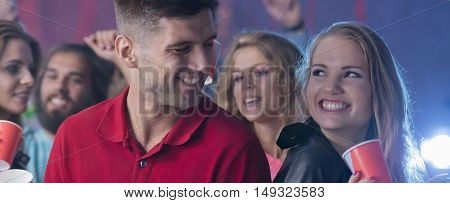 Young couple looking at each other with other people at the background