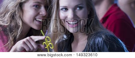 Closer shot of a young woman talking something to her smiled friend
