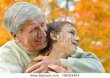 Grandfather and grandson together in autumn park
