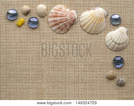 Sea theme background frame with seashells, scallops and blue glass pebbles on the rough weave textile mat