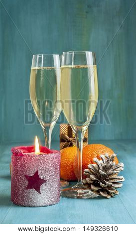 Photo for Christmas or New Year card. Two glasses of sparkling wine, burning candle with star shape on it, pine cone with snow, tangerines, and little present box in the background. Selective focus
