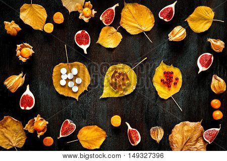 Concept of cold autumn - pills, leaves on dark wood. Colorfull pattern