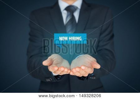 Now hiring - human resources concept. Businessman (recruiter, HR staffer) hold virtual label with text.