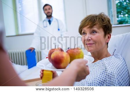 Nurse serving a breakfast to patient in hospital