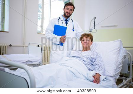 Portrait of smiling doctor and patient looking at camera in hospital