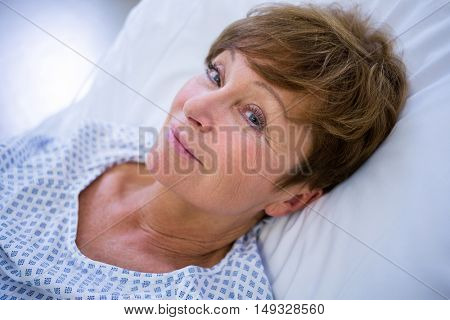 Portrait of smiling patient lying on bed in hospital