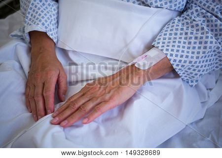 Close-up of patients hand with iv drip in hospital room
