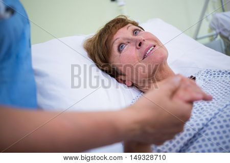 Senior patient talking to a nurse in hospital room