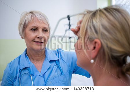Nurse checking patient temperature in hospital room