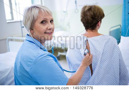 Portrait of nurse examining a patient with a stethoscope in hospital ward