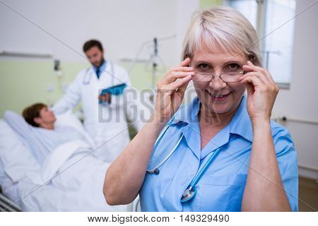 Portrait of smiling nurse wearing spectacle in hospital room