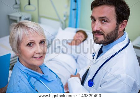 Portrait of smiling doctor and nurse standing in hospital room