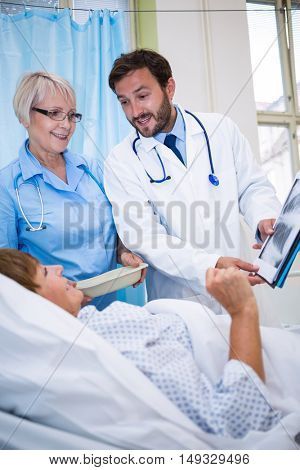 Doctors showing medical report to senior patient in hospital room