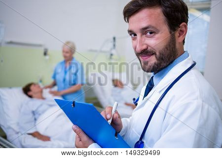 Portrait of smiling doctor checking a medical report in hospital room
