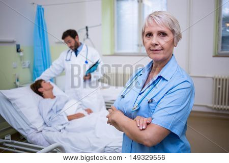 Portrait of nurse standing with arms crossed in hospital room