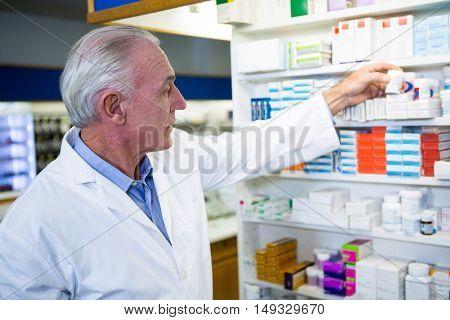 Pharmacist checking a bottle of drug in pharmacy