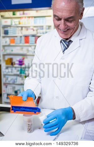 Pharmacist putting pills in container at pharmacy