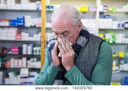 Customer covering his nose with handkerchief while sneezing in pharmacy