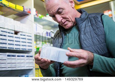 Customer checking a pill box in pharmacy