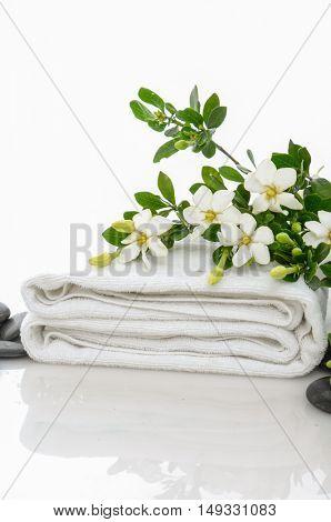 gardenia on towel with black stones